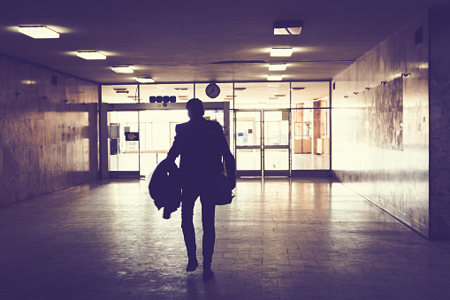 Silhouette of man walking through an empty hallway.