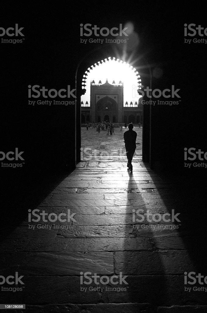 Silhouette of Man Walking Through Mosque royalty-free stock photo