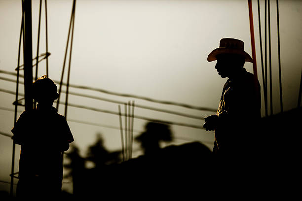 SIlhouette of Man Wearing Cowboy Near Wires stock photo