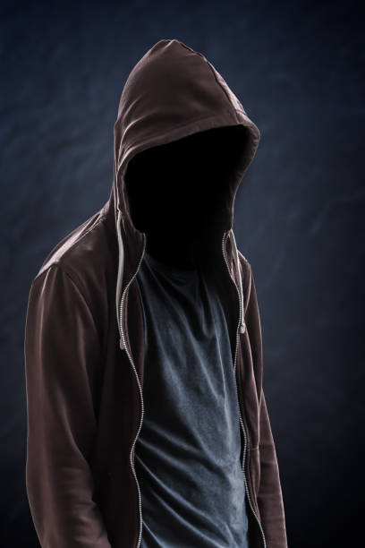 Silhouette of man with a hood and face in the dark, black background with copy space, criminal or hacker concept Silhouette of man with a hood and face in the dark, black background with copy space, criminal or hacker concept creepy stalker stock pictures, royalty-free photos & images