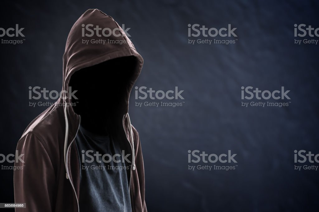 Silhouette of man with a hood and face in the dark, black background with copy space, criminal or hacker concept stock photo