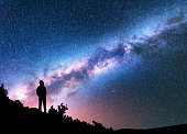 Silhouette of man with backpack on the hill against colorful Milky Way at night. Space background. Landscape with man, bright milky way, sky with stars. Beautiful galaxy. Travel. Starry sky. Universe