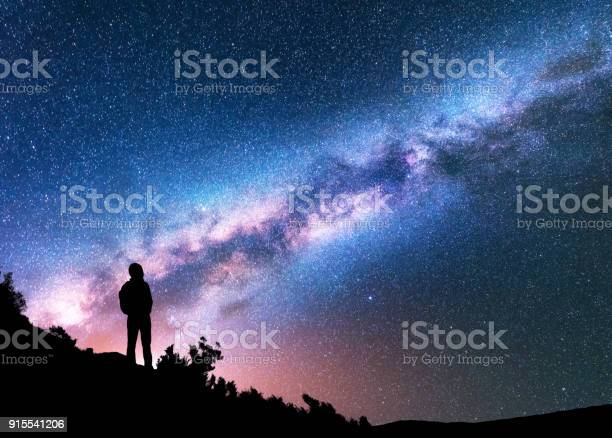 Photo of Silhouette of man with backpack on the hill against colorful Milky Way at night. Space background. Landscape with man, bright milky way, sky with stars. Beautiful galaxy. Travel. Starry sky. Universe