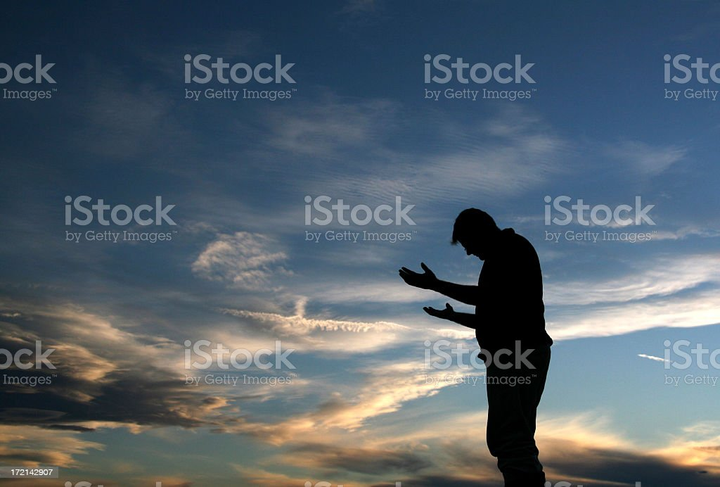 Silhouette of Man With Palms Open Meditating royalty-free stock photo