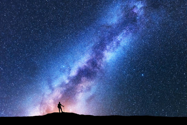 Silhouette of man with trekking poles against amazing Milky Way at night. Space background. Landscape with man on the hill, bright milky way, sky with stars. Beautiful galaxy. Travel. Starry sky Silhouette of man with trekking poles against amazing Milky Way at night. Space background. Landscape with man on the hill, bright milky way, sky with stars. Beautiful galaxy. Travel. Starry sky milky way stock pictures, royalty-free photos & images