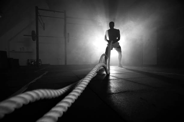 Silhouette of man working out with battle ropes stock photo