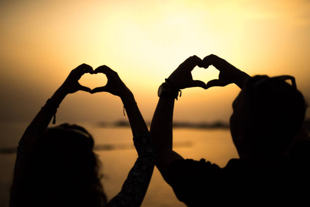 Silhouette of mature couple making heart shapes with hands on sunset. stock photo
