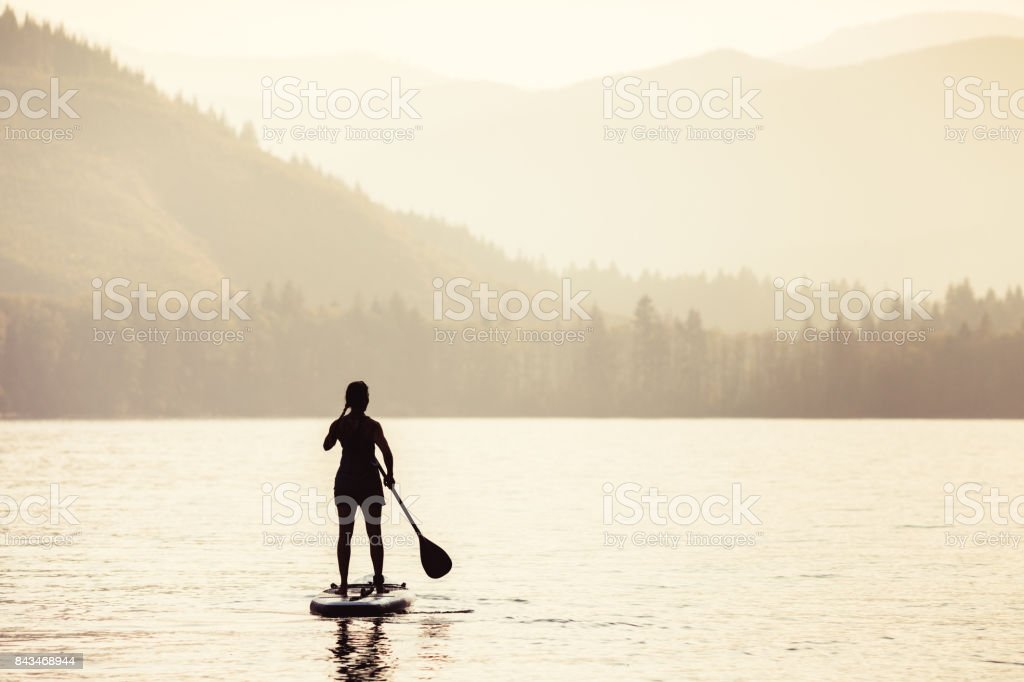 Silhouette of Mature Woman Paddleboarding stock photo
