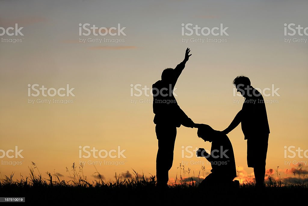 Silhouette of Men Praying stock photo