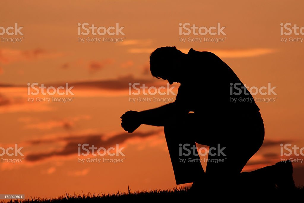 Silhouette of Middle Aged Male Saying A Prayer stock photo