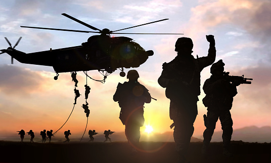 silhouette  of military operation at sunset with sun glare