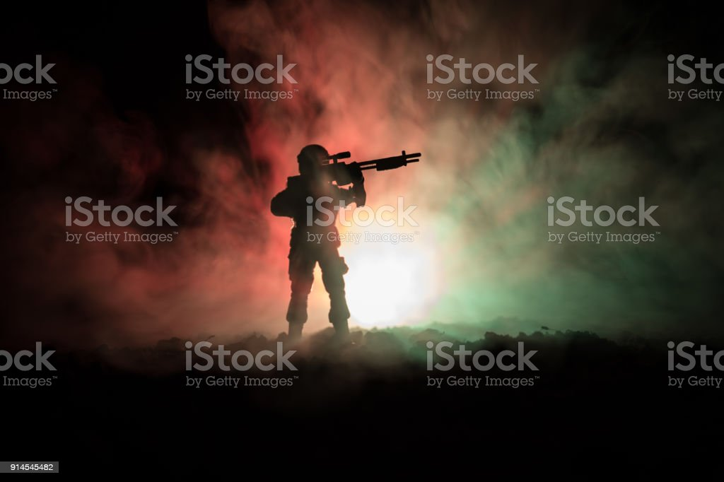 Silhouette of military sniper with sniper gun at dark toned foggy background. shot, holding gun, colorful sky, background stock photo