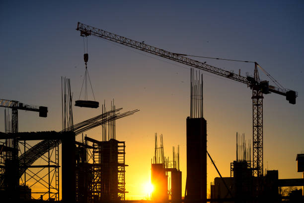 Silhouette of modern construction site at dusk stock photo