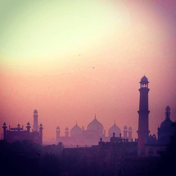 Silhouette of mosques Silhouette of mosque and minarets show as the sunsets on a hazy day in Lahore, Pakistan lahore pakistan stock pictures, royalty-free photos & images