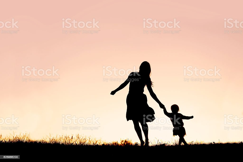 Silhouette of Mother and Baby Daughter Running and Dancing at Sunset stock photo