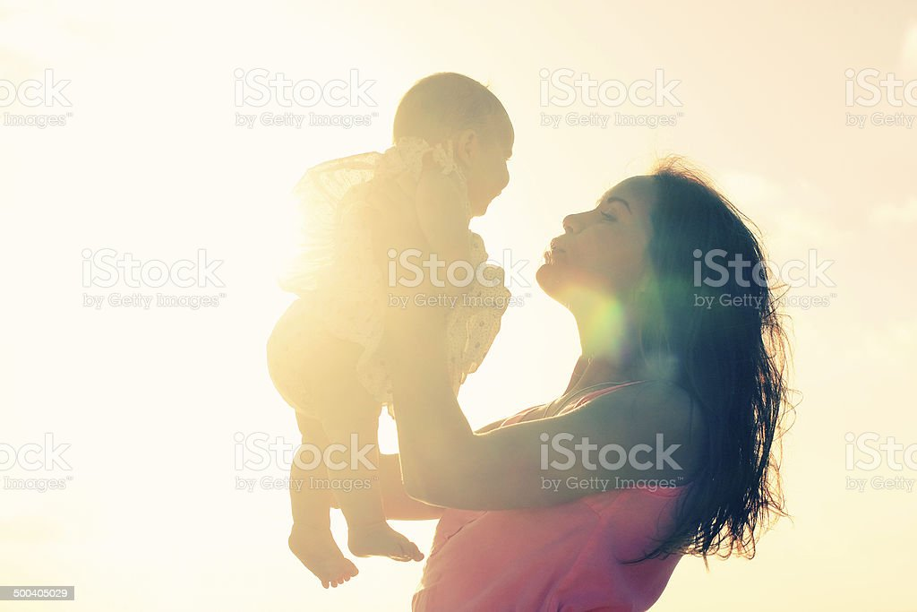 Silhouette of mother and baby stock photo