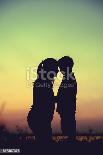 istock Silhouette of mother and child enjoying at riverside. 657307376