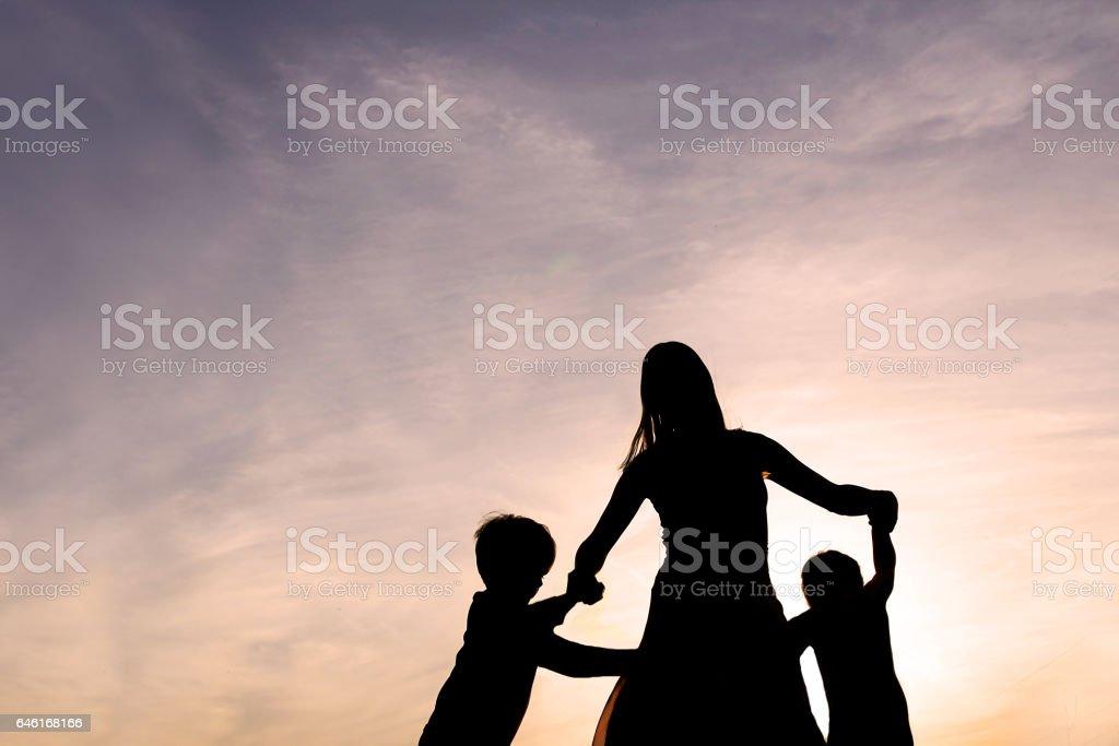 Silhouette de mère et enfants dansant au coucher du soleil - Photo