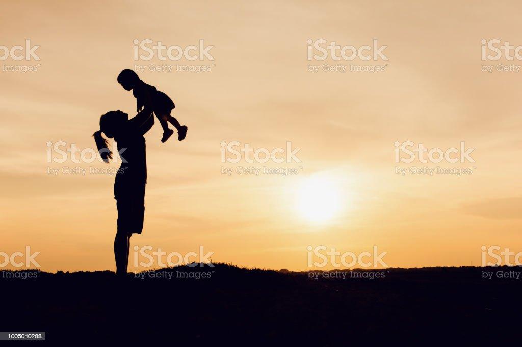 Fotografía De Silueta De Madre E Hija Elevación A Niño Aire