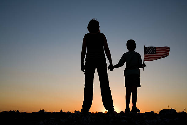 Silhouette of mother and son on horizon during sunset stock photo