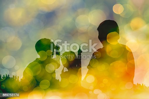 istock Silhouette of mother and two kids on bokeh abstract in yellow background 889253174