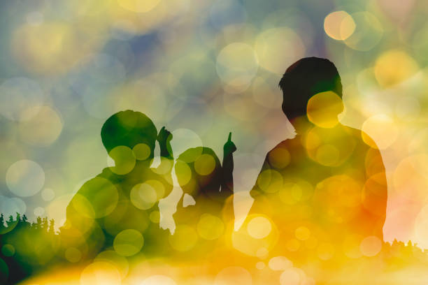 Silhouette of mother and two kids on bokeh abstract in yellow background stock photo