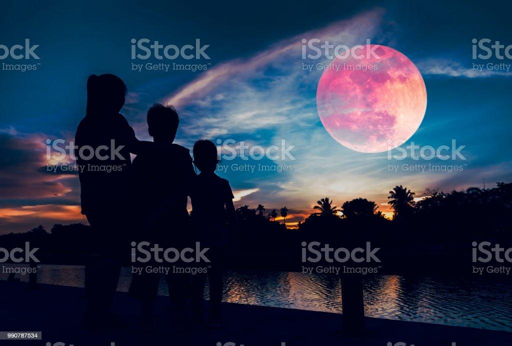 Silhouet van moeder met kinderen rood super maan aan de hemel te kijken. foto