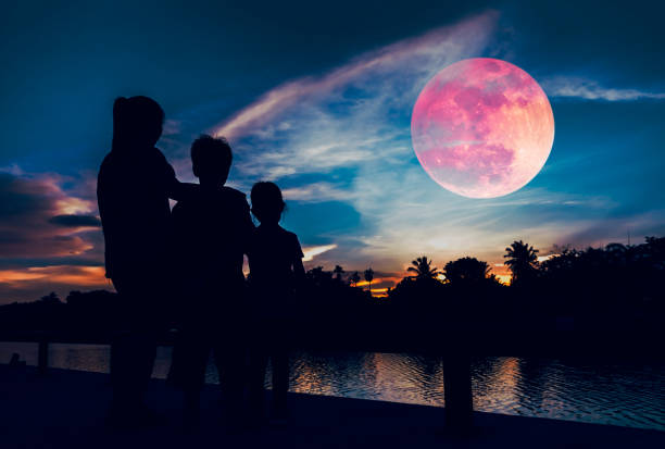 Silhouette of mother with children looking at red super moon on sky. stock photo