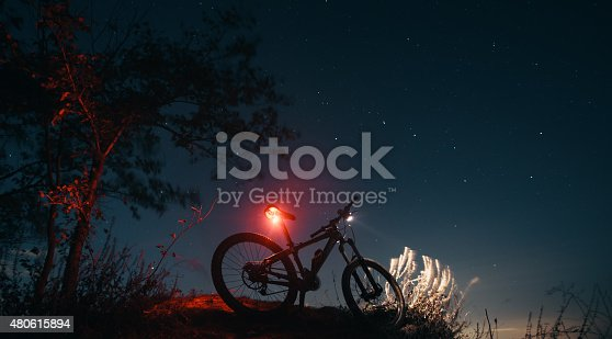 istock Silhouette of mountain bicycle with glowing lamps 480615894