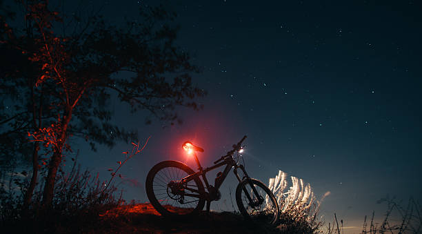 Silhouette of mountain bicycle with glowing lamps Silhouette mountain bicycle on a background of the sky.  big dipper constellation stock pictures, royalty-free photos & images