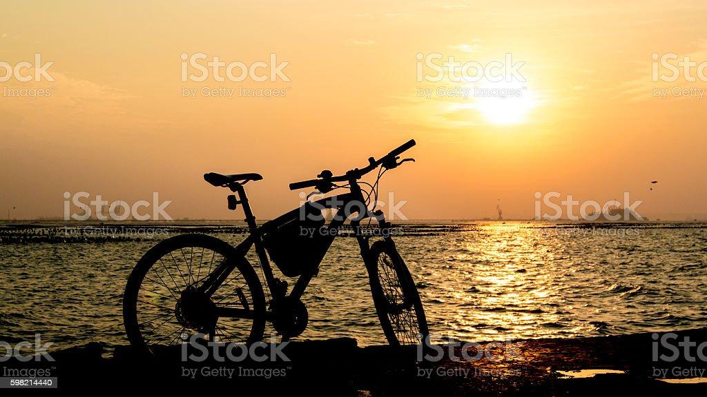 Silhueta de montanha bicicleta no fundo do mar com um pôr do sol foto royalty-free
