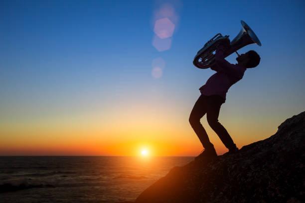 Silhouette der Musiker spielen Tuba am Meeresufer im traumhaften Sonnenuntergang. – Foto
