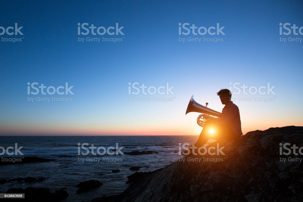 Silhouette of musician play Tuba on sea shore at sunset . stock photo
