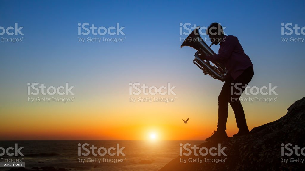 Silhouette of musician play Tuba on sea shore at sunset. stock photo