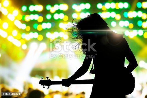 Silhouette of musician playing on guitar on concert stage