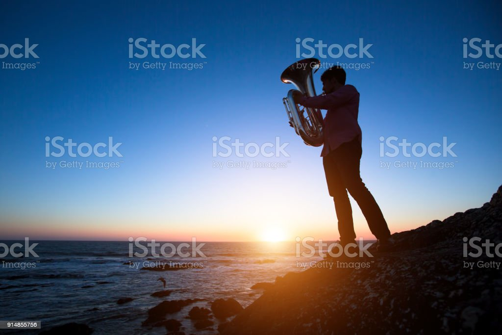 Silhouette of musician with Tuba on rocky sea coast during sunset. stock photo