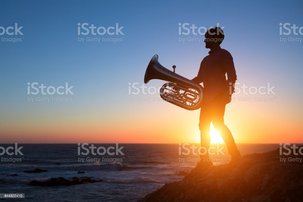 Silhouette of musician with Tuba on sea shore at sunset . stock photo