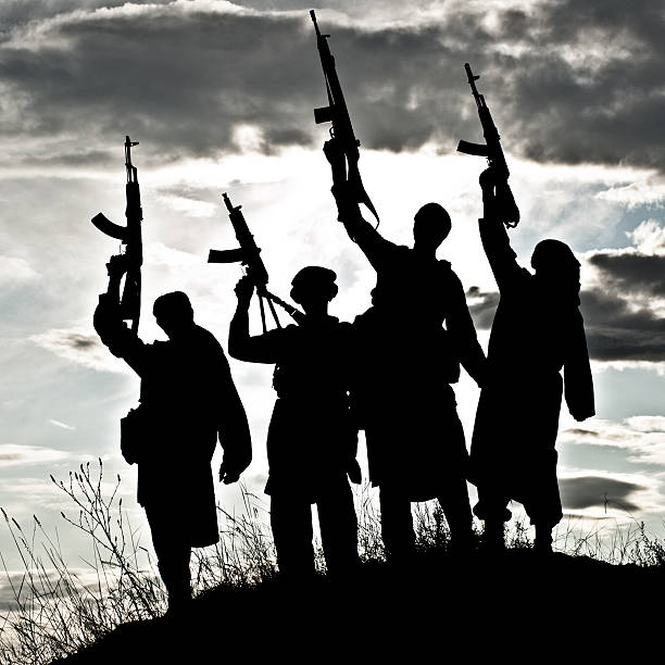 Silhouette of Muslim militants with rifles Silhouette of several muslim militants with rifles terrorism stock pictures, royalty-free photos & images