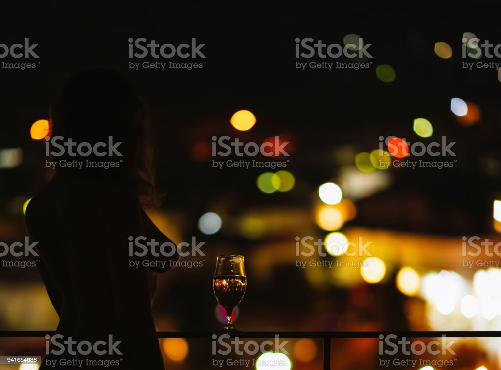 Silhouette of naked woman on the balcony with a glass of wine on the background of a night city stock photo