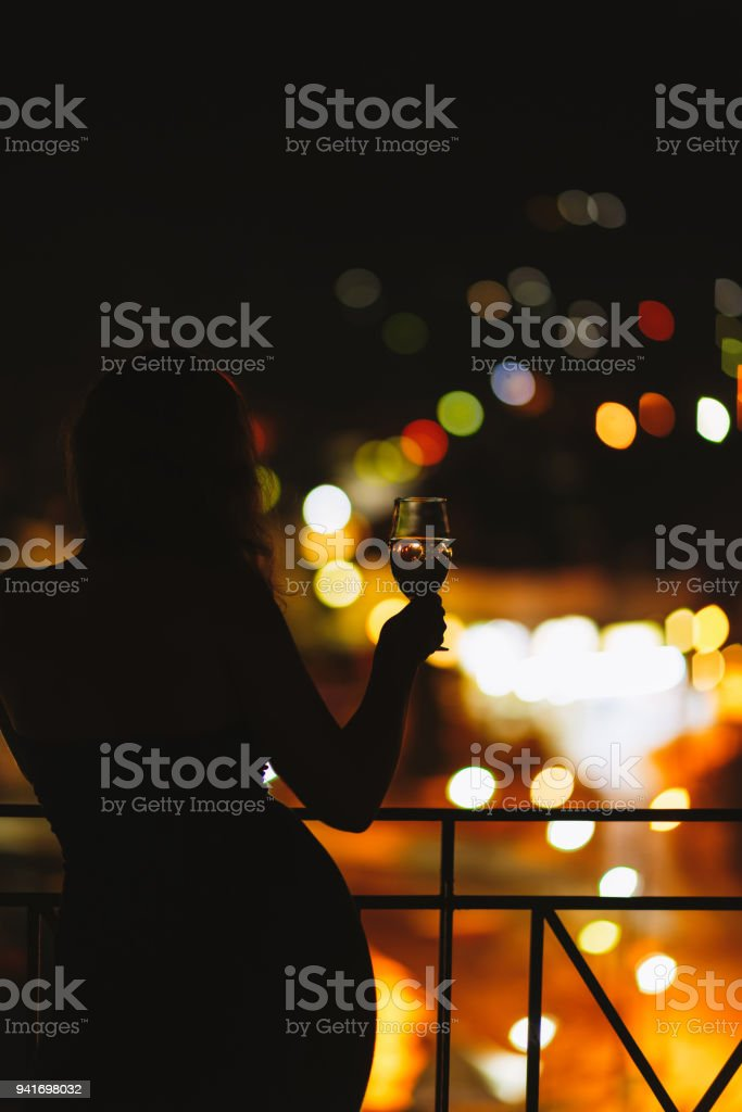 Silhouette of naked woman on the balcony with a glass of wine on the...