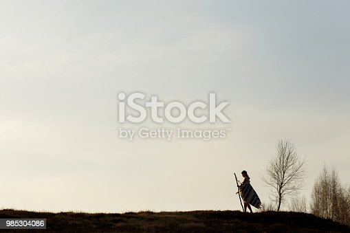 silhouette of native indian american woman walking on hill among trees in sunset evening mountains