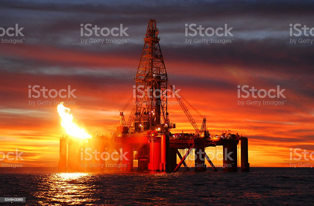 Silhouette of ocean oil rig at sunset. stock photo