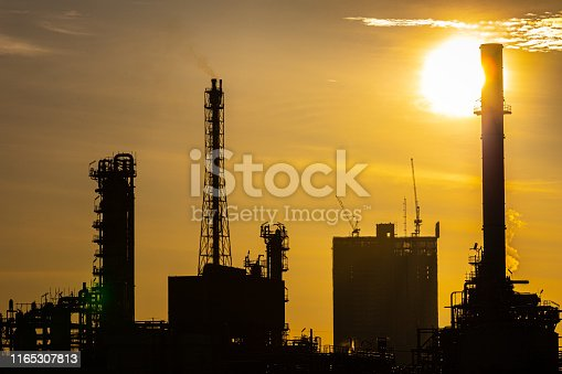 istock Silhouette of oil and gas refinery industry plant with glitter lighting and sunrise in the morning, Factory of petroleum industrial, Power plant,Energy power station area. 1165307813