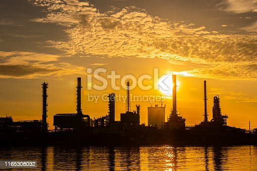 istock Silhouette of oil and gas refinery industry plant with glitter lighting and sunrise in the morning, Factory of petroleum industrial, Power plant,Energy power station area. 1165308032