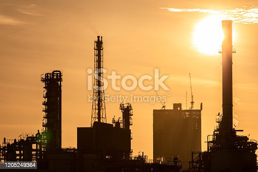 istock Silhouette of oil and gas refinery industry plant with glitter lighting and sunrise in the morning, Factory of petroleum industrial, Power plant,Energy power station area. 1205249364