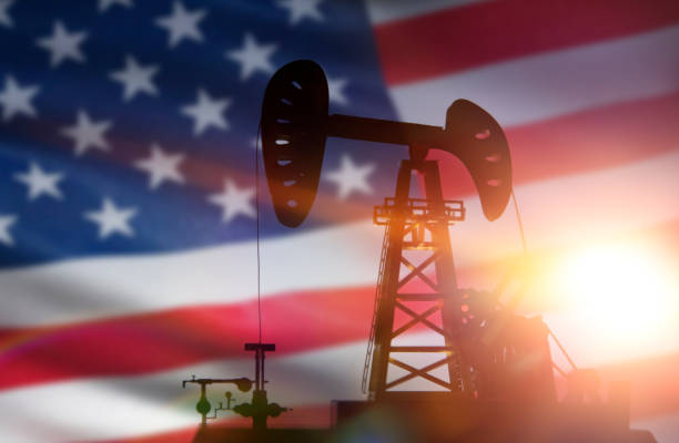 silhouette of oil drilling pump on background of united states flag. stock photo