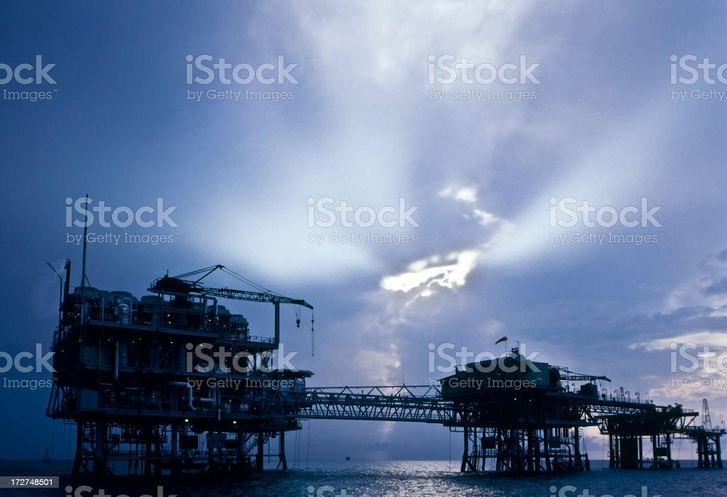 Silhouette of oil facilities at sunset royalty-free stock photo