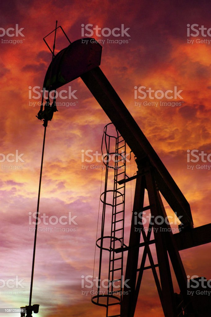 Silhouette of Oil Pump Against Colorful Sunrise royalty-free stock photo