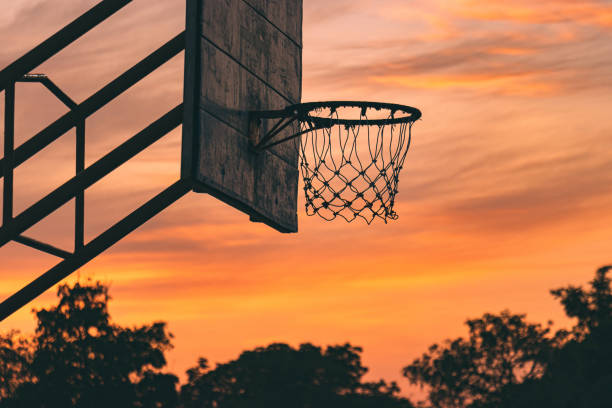 silhouette of old outdoor basketball court with dramatic sky in the sunrise morning stock photo