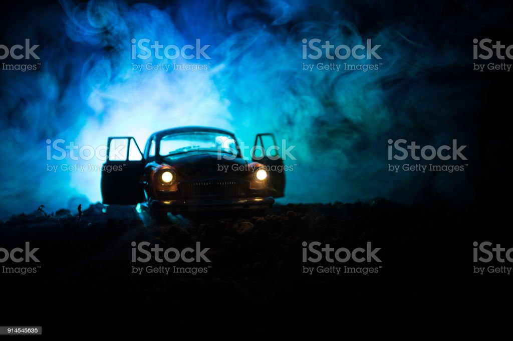 Silhouette of old vintage car in dark foggy toned background with glowing lights in low light, or silhouette of old crime car dark background. stock photo